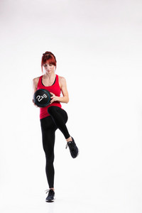 Attractive young fitness woman in red tank top, holding medicine ball, lifting leg. Studio shot on gray background.