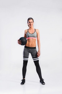 Attractive young fitness woman in sports bra and black leggings holding medicine ball. Slim waist, perfect fit female body. Studio shot on gray background.