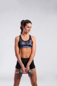 Attractive young fitness woman in sports bra and black shorts, holding dumbbell. Slim waist, perfect fit female body. Studio shot on gray background.