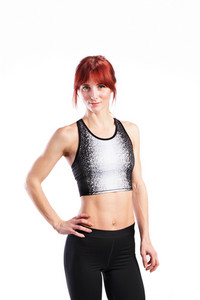 Attractive young fitness woman in sports bra and leggings. Studio shot on gray background.