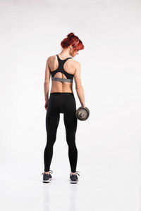 Attractive young fitness woman in sports bra and leggings, working out with barbell. Studio shot on gray background. Rear view.