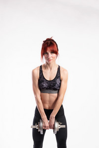 Attractive young fitness woman in sports bra and leggings, working out with barbell. Studio shot on gray background.