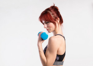 Attractive young fitness woman in sports bra, working out with barbell. Studio shot on gray background.