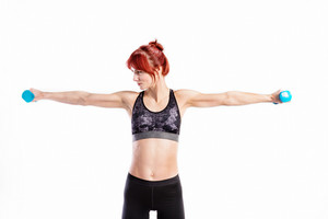 Attractive young fitness woman in sports bra, working out with barbells. Studio shot on gray background.