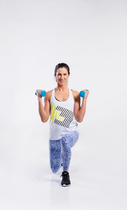 Attractive young fitness woman in white singlet, working out with dumbbells, doing lunges. Slim waist, perfect fit female body. Studio shot on gray background.