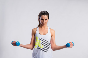 Attractive young fitness woman in white singlet, working out with dumbbells. Slim waist, perfect fit female body. Studio shot on gray background.