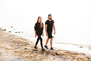 Attractive young man and woman walking on the beach together wearing sports clothing