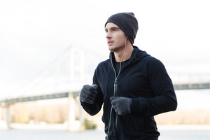 Attractive young man athlete in earphones listening to music and running outdoors