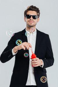 Attractive young man in sunglasses and black suit blowing soap bubbles over grey background