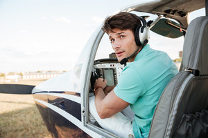 Attractive young man pilot sitting in cabin of small airplane
