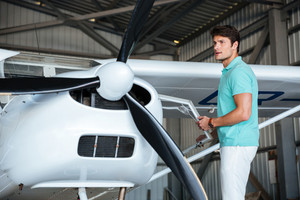 Attractive young man pilot standing near small private airplane