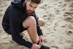 Attractive young man preparing for jogging on the beach. from above portrait