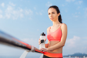 Attractive young sportswoman with bottle of water standing outdoors