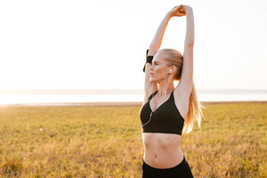 Attractive young woman athlete stretching hands outdoors in the morning