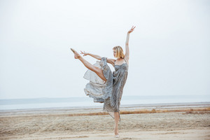 Attractive young woman ballerina in long dress dancing on the beach