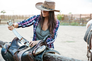 Attractive young woman cowgirl in hat standing and preparing saddle for riding horse