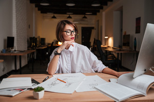 Attractive young woman fashion designer in glasses sitting and working in office