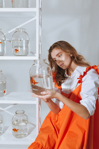 Attractive young woman holding and looking at gold fish in jar