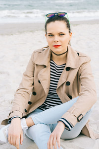 Attractive young woman in a coat, jeans and striped t-shirt sitting on a beach, vertical framing