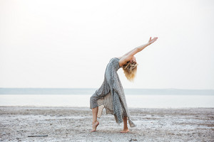 Attractive young woman in dress dancing on the beach