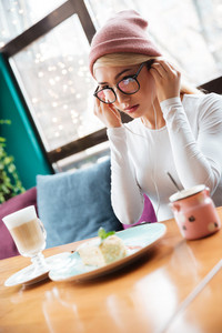 Attractive young woman in hat and glasses eating and listening to music with earphones in cafe