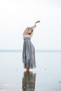 Attractive young woman in long dress standing in lake