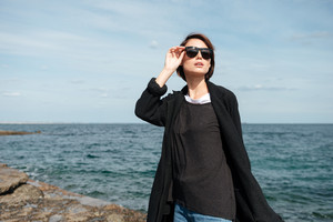 Attractive young woman in sunglasses and black coat walking near the sea in autumn