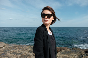 Attractive young woman in sunglasses standing on the seaside in windy weather