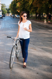 Attractive young woman in sunglasses walking with bicycle and takeaway coffee