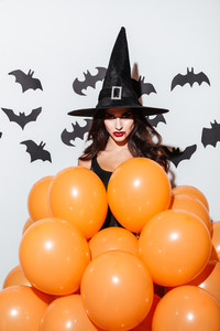 Attractive young woman in witch halloween costume with orange balloons over white background
