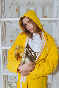 Attractive young woman in yellow raincoat standing and holding jar with gold fish