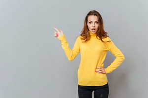 Attractive young woman in yellow sweater pointing finger up over gray background