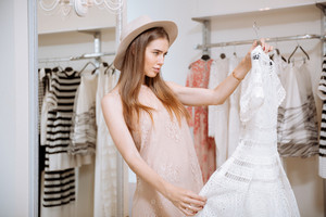Attractive young woman looking at beautiful white dress and thinking in clothing store