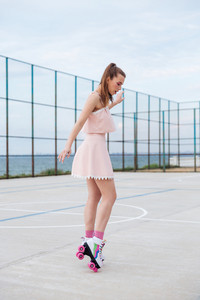 Attractive young woman on roller skates standing and having fun at the plagroung
