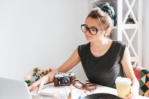 Attractive young woman photogtrapher in glasses drinking coffee and using laptop at the table in the room