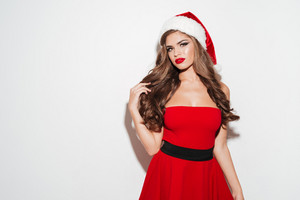 Attractive young woman posing in red santa claus costume and hat isolated over white background