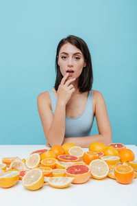 Attractive young woman sitting at the table with oranges and grapefruits and touching her lips over blue background