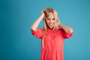 Attractive young woman touching her hair and looking at camera isolated on a blue background