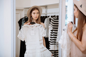 Attractive young woman trying on dress in front of mirror in clothing store