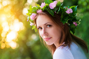 Attractive young woman with flower wreath on her head with sunset in background.