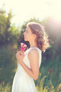 Attractive young woman with flowers outside on a meadow.