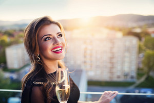 Attractive young woman with glass of champagne in a bar
