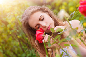 Attractive young woman with rose outside in a garden.