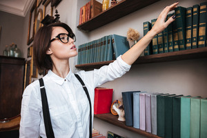 Authoress in glasses and white shirt selecting the book on bookshelf. Side view