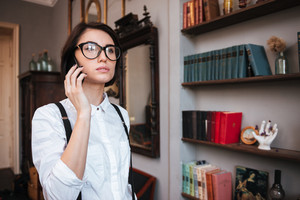 Authoress in glasses and white shirt talking on phone and looking away