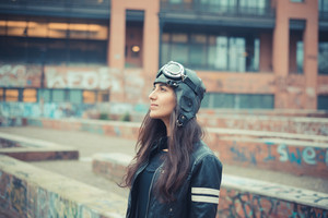 aviator young beautiful brunette woman with cap and glasses in the city