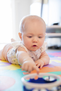 Baby girl with blue eyes playing on mat at floor