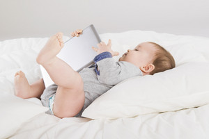 Baby with digital tablet is playing in the bed