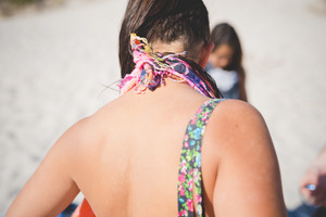 back of young beautiful tanned woman at the beach in summertime