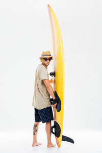 Back view a young surfer holding surfboard and looking over his shoulder isolated on the white background